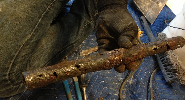 An old, corroded pipe with major signs of leaks requires home repiping.